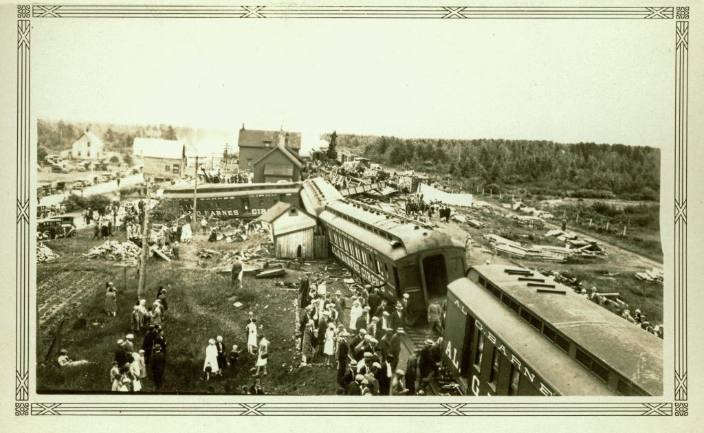 Black-and-white photo of a derailed train, with people standing around.