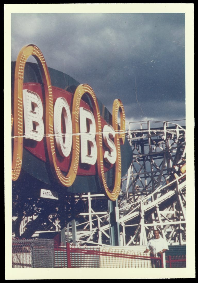 "Color photograph of ""The Bobs"" ride sign. ""Bobs"" is written in white in all capitals, which an oranage line curving up and down between each letter. The letters and line have lightbulbs in them to illuminate them at night."