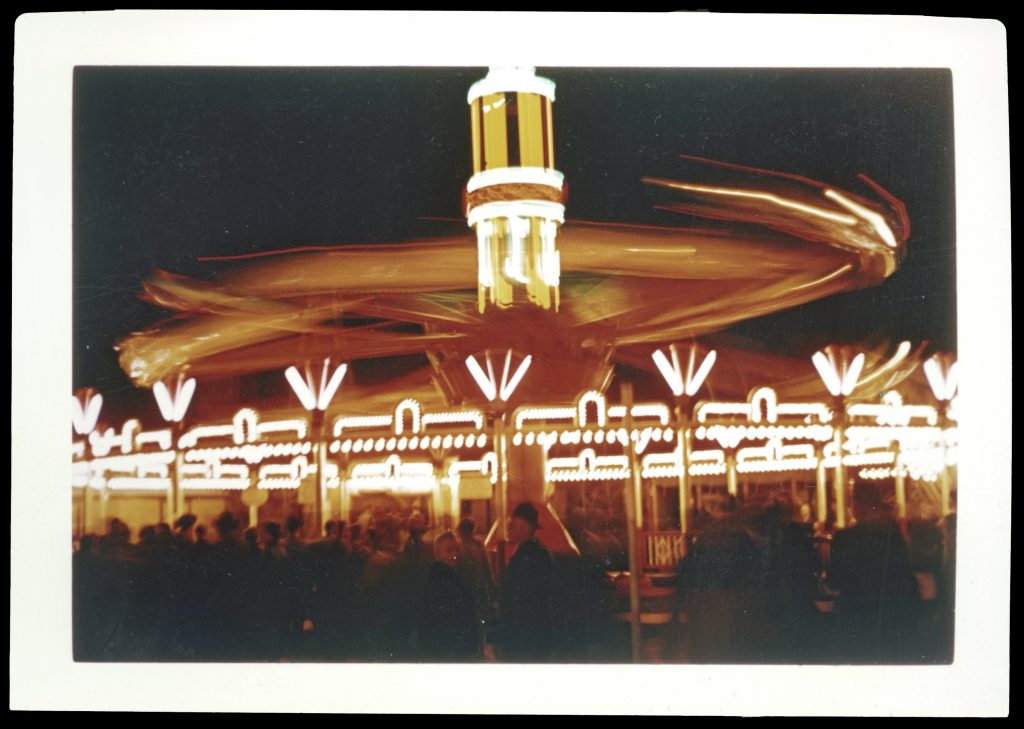 Color photograph of a carousal at night, with a crowd of people in front.