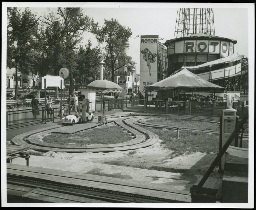 "Black-and-white photograph of rides at Riverview Park. In the foregroudn is a ride with toy cars on a track. In the rear are signs for the ""Rotor"" ride."