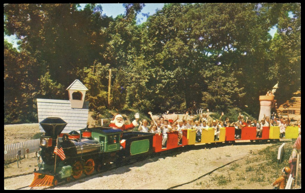 Postcard photograph of a miniature train. A man dressed as Santa sits in the first car, while all the others are filled with White children, waving.
