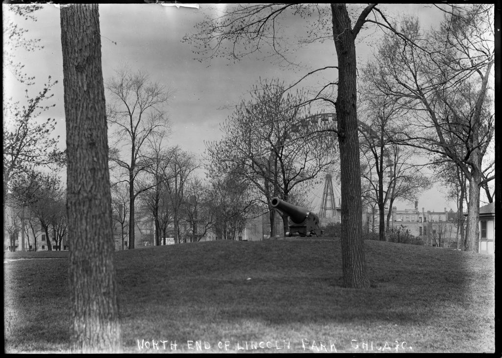 Black-and-white photograph of a Ferris Wheel through some trees. A decorative cannon sits on the grass in the foreground
